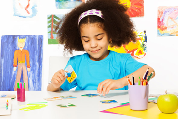 African girl putting matching cards during developmental game on table while sitting in playroom with wall behind full of children drawings