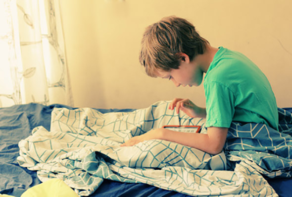 7 year old boy lies in bed and plays with a laptop