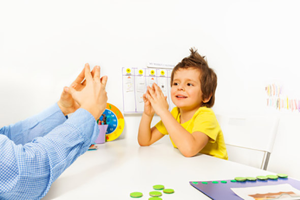 Smiling boy exercises putting hands and fingers together with therapist improving motor skills sitting opposite at the table indoors